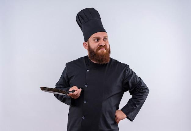 Ein nachdenklicher bärtiger kochmann in der schwarzen uniform, die schwarze pfanne hält und seite mit händen auf taille auf einer weißen wand schaut