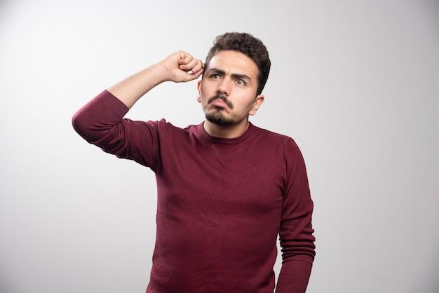 Ein nachdenklicher brünetter mann, der steht und posiert
