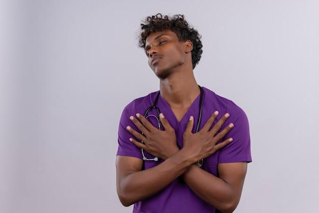 Ein nachdenklicher junger gutaussehender dunkelhäutiger arzt mit lockigem haar in violetter uniform und stethoskop, das hände auf seiner brust hält