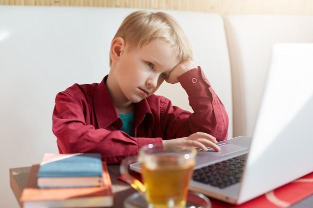 Ein nachdenklicher kleiner junge mit blonden haaren, die ein rotes hemd tragen und gelangweilt aussehen