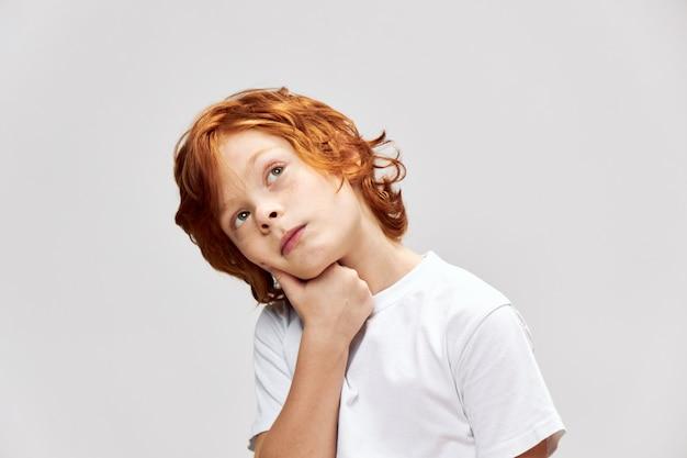 Ein nachdenklicher rothaariger junge hält seine hand auf seinem gesicht und schaut nach oben, um etwas zu planen