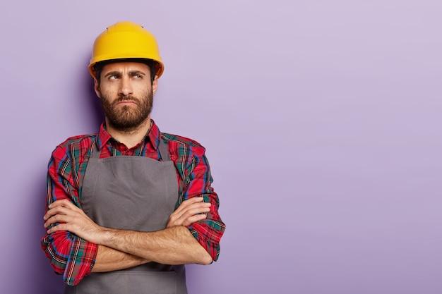 Ein nachdenklicher, unzufriedener industriearbeiter trägt einen gelben helm und eine schürze