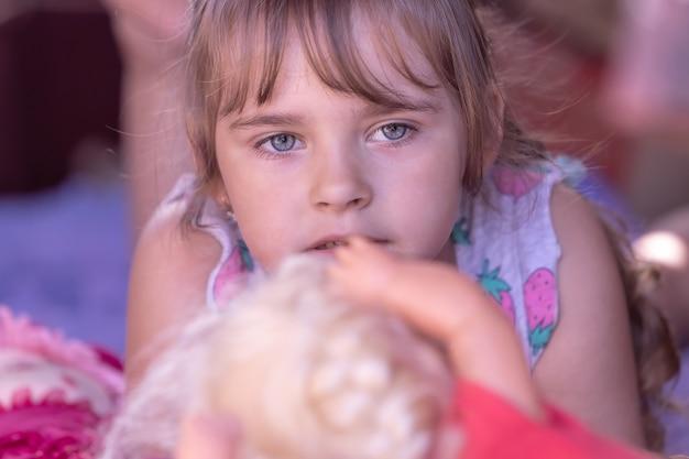 Ein nachdenkliches kleines mädchen, ein kind, liegt neben einem spielzeug und ist bereit zu weinen