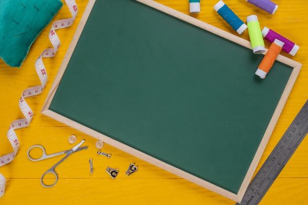 Ein nähzeug, eine nadel, ein faden, eine nadel, platziert auf einen gelben bretterboden.