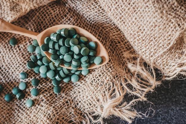 Ein nahaufnahmebild eines löffels mit spirulina auf einem sackleinenhintergrund. super essen. veganes essen. seetang.