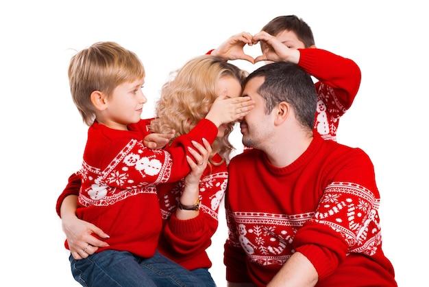 Ein nahaufnahmefoto der jungen familie, die spaßzeit zusammen in der weihnachtskleidung hat
