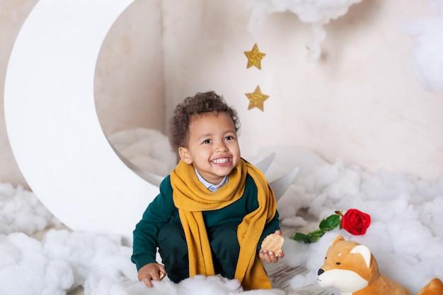 Ein nahaufnahmeporträt des gesichts eines afroamerikanischen jungen. kleiner junge sitzt und lächelt. süßes baby, baby im spiel. hübsches lächeln. lockige haare. kindheit. kind spielt im kindergarten. vorschulerziehung für kinder