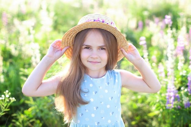 Ein nahaufnahmeporträt eines kleinen niedlichen mädchens mit langen haaren und strohhut spielt auf einem blühenden lupinenfeld. kindheitskonzept. speicherplatz kopieren. kinder und natur. kinder auf dem land. sommerurlaub. romantik