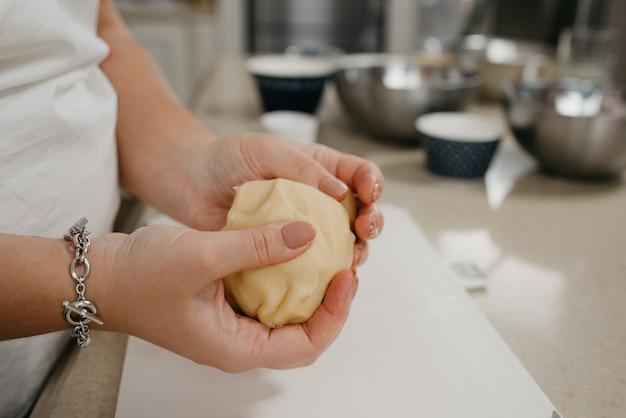 Ein nahes foto der hände einer frau, die shortbread teig in der küche hält