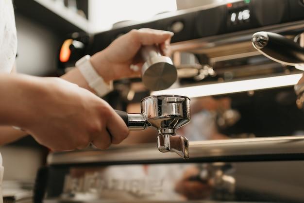 Ein nahes foto von weiblichen händen, die einen metallstampfer und einen siebträger mit kaffee in einem café halten. ein barista, der das pressen von gemahlenem kaffee zum brauen von espresso oder americano in einem café vorbereitet.