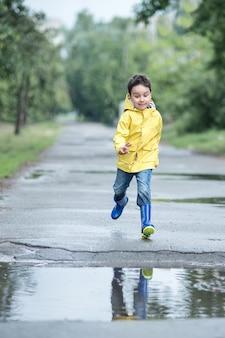 Ein nasses kind springt in eine pfütze.
