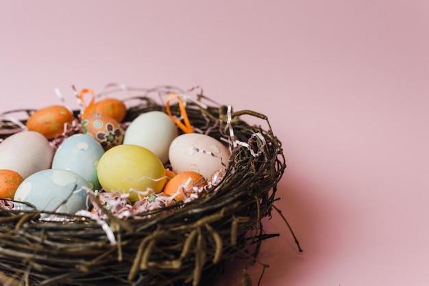 Ein nest aus zweigen und heu und ein rosa papierfüller mit pastellfarbenen ostereiern. bemalte und dekorative eier für einen leichten osterurlaub. osterkarte auf einem rosa hintergrund