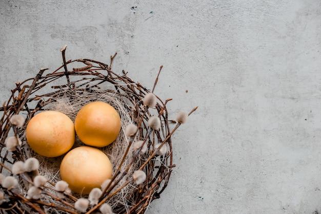 Ein nest und mehrere eier mit weidenruten. abstrakter grauer steinhintergrund, glückliches ostern-konzept
