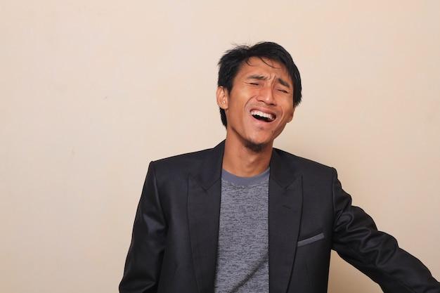 Ein netter asiatischer junger mann mit einem ausdruck auf gelächter, einen anzug mit einer inneren strickjacke tragend
