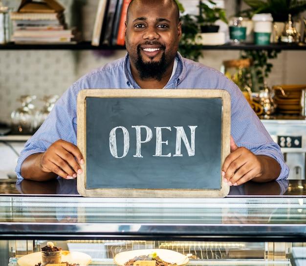 Ein netter kleinunternehmer mit offenem zeichen