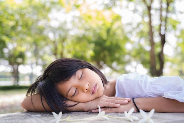 Ein nettes asiatisches mädchen, das im grünen park im freien mit unscharfem hintergrund schläft