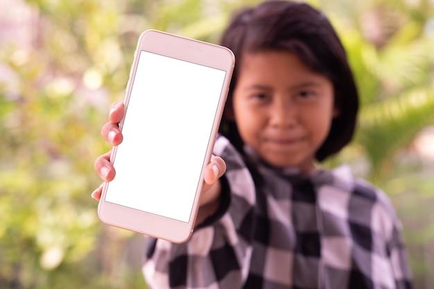 Ein nettes kleines asiatisches mädchen, das smartphone mit weißem leerem bildschirm zeigt
