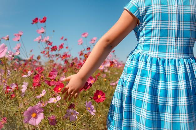 Ein nettes kleines mädchen auf einem rosa blumenfeld am frühlingstag.