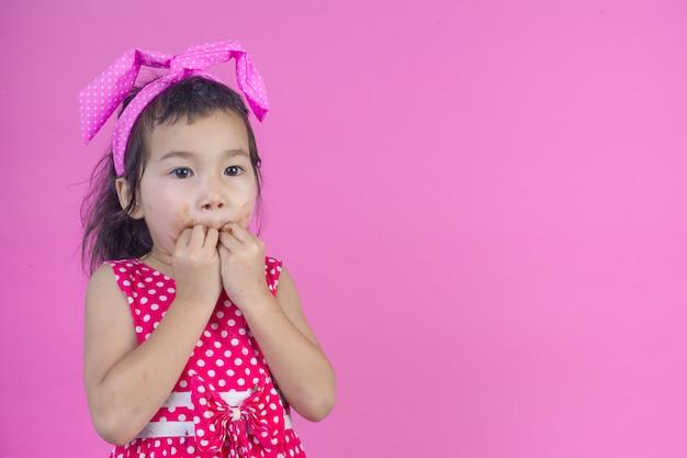 Ein nettes mädchen, das ein rotes gestreiftes hemd isst eine schokolade mit einem schmutzigen mund auf dem rosa trägt.
