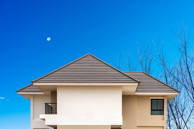 Ein neues dach des hauses mit blauem himmel errichten.