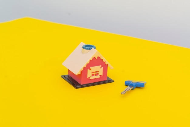 Ein neues kleines spielzeughaus mit schlüsselpaar konzept des neuen wohnungskaufs
