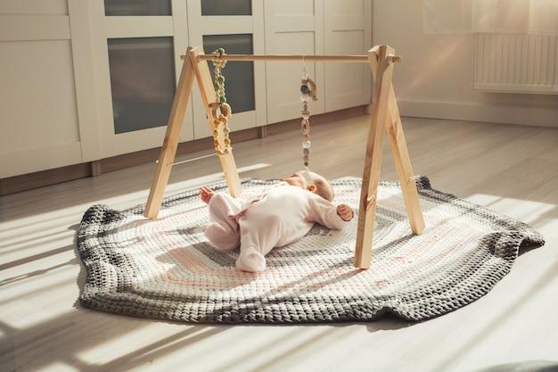 Ein neugeborenes baby liegt auf einem gestrickten teppich. baby spielt mit simulator