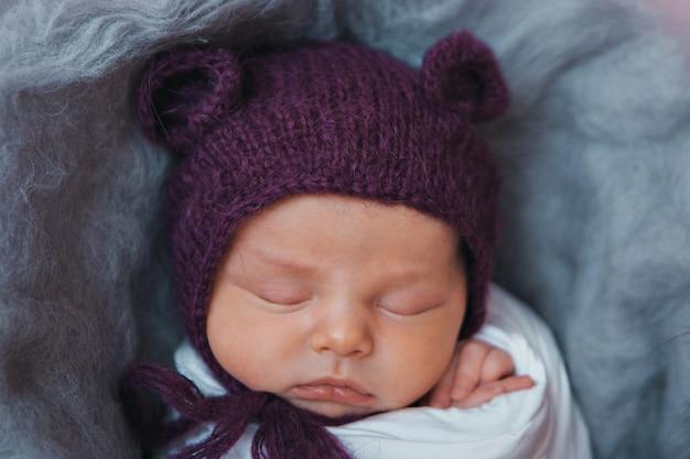 Ein neugeborenes in einer strickmütze mit ohren. nachahmung eines babys im mutterleib. porträt eines neugeborenen .. das konzept der gesundheit, elternschaft, kindertag, medizin, ivf, mode