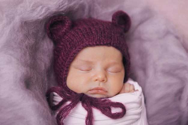 Ein neugeborenes in einer strickmütze mit ohren. nachahmung eines babys im mutterleib. porträt eines neugeborenen .. das konzept der gesundheit, elternschaft, kindertag, medizin, ivf