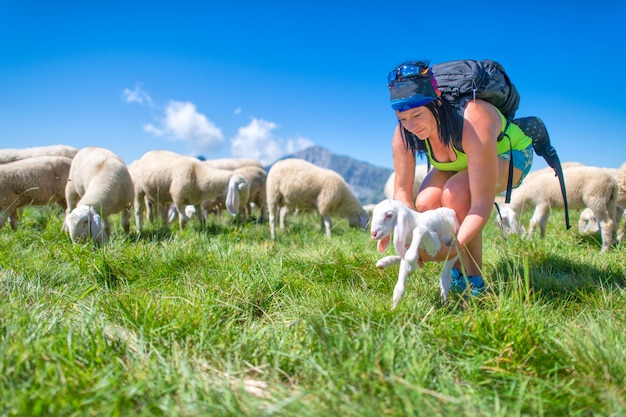 Ein neugeborenes lamm, das der herde von einer sportlichen frau geschenkt wurde