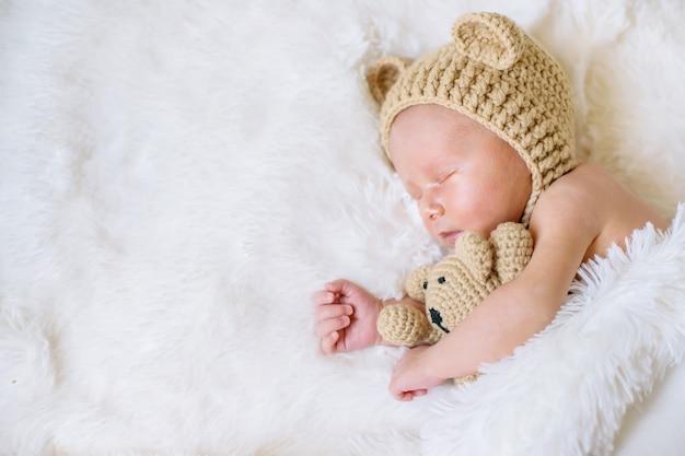 Ein neugeborenes schläft mit einem teddybär