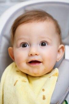 Ein neun monate altes lächelndes baby sitzt an einem weißen tisch in einem hochstuhl und isst mit einem löffel aus einer schüssel. mama füttert das baby mit einem löffel. unscharfer hintergrund. gesundes essen für kinder. kinder essen.