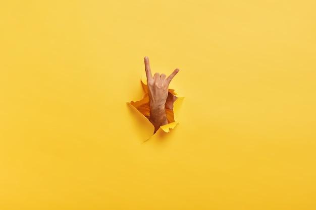 Ein nicht wiederzuerkennender mann macht eine rock'n'roll-geste durch ein zerrissenes loch in gelbem papier. männchen zeigt hornzeichen mit der hand, die in spaltschlitz des papiers gestreckt wird. körpersprachenkonzept. farbiger raum