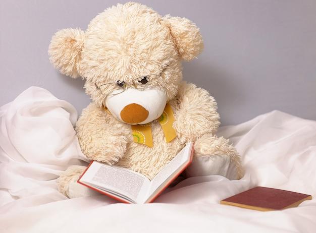 Ein niedlicher beige teddybär, damit kinder mit brille spielen, liest ein buch