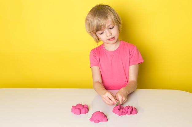Ein niedlicher entzückender junge der vorderansicht im rosa t-shirt spielt mit buntem kinetischem sand