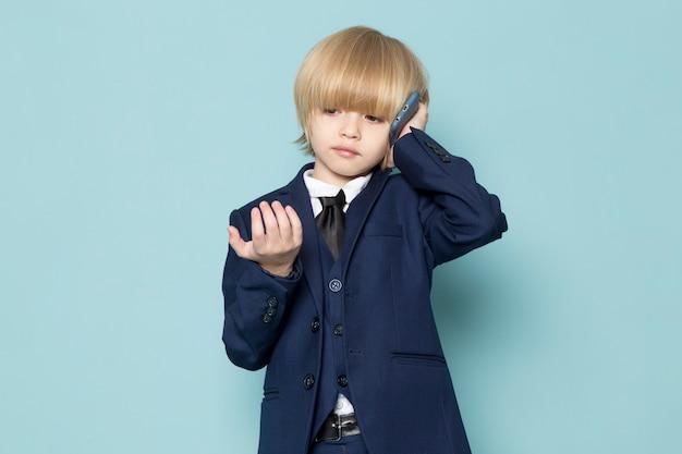 Ein niedlicher geschäftsjunge der vorderansicht im blauen klassischen anzug, der auf der telefongeschäftsarbeitsmode spricht