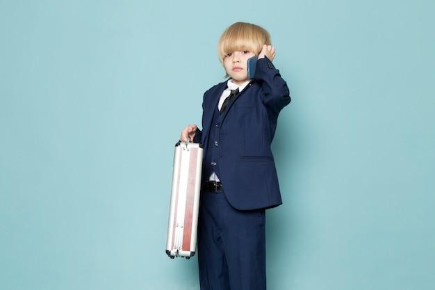 Ein niedlicher geschäftsjunge der vorderansicht im blauen klassischen anzug, der den braun-silbernen koffer hält, der auf der geschäftsmode des telefongeschäfts spricht