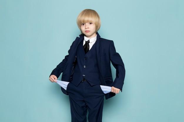 Ein niedlicher geschäftsjunge der vorderansicht im blauen klassischen anzug, der seine geschäftsarbeitsmode seiner taschen zeigt