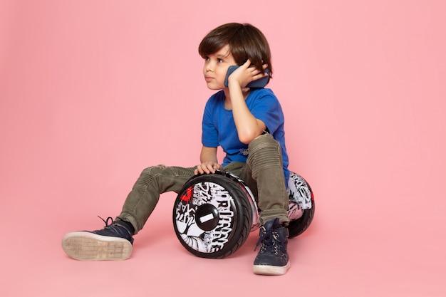 Ein niedlicher junge der vorderansicht, der am telefon im blauen t-shirt spricht, das segway auf dem rosa boden reitet