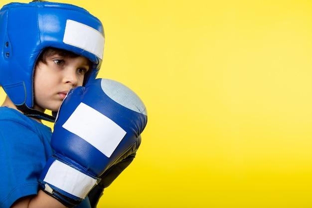 Ein niedlicher junge der vorderansicht, der im blauen helm und in den blauen handschuhen an der gelben wand boxt