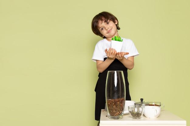 Ein niedlicher junge der vorderansicht, der mit der kleinen grünen pflanze nahe tisch mit kaffee und tassen auf dem steinfarbenen boden lächelt
