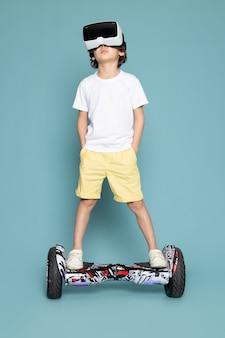 Ein niedlicher junge der vorderansicht, der vr auf dem segway im weißen t-shirt auf dem blauen boden spielt