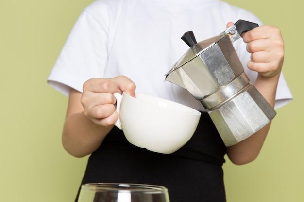 Ein niedlicher junge der vorderansicht im weißen t-shirt, das kaffeegetränk vorbereitet