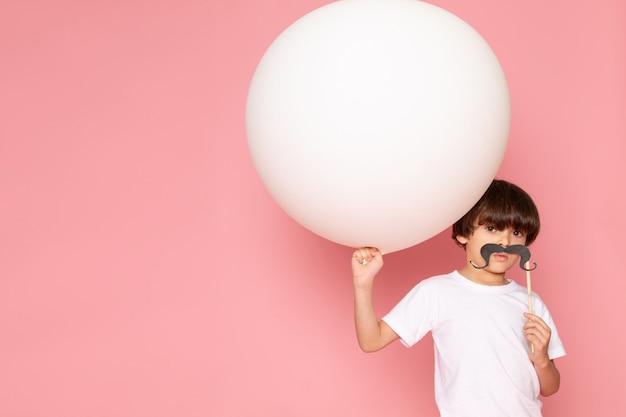 Ein niedlicher junge der vorderansicht im weißen t-shirt mit schnurrbart, der weißen ball auf dem rosa boden hält
