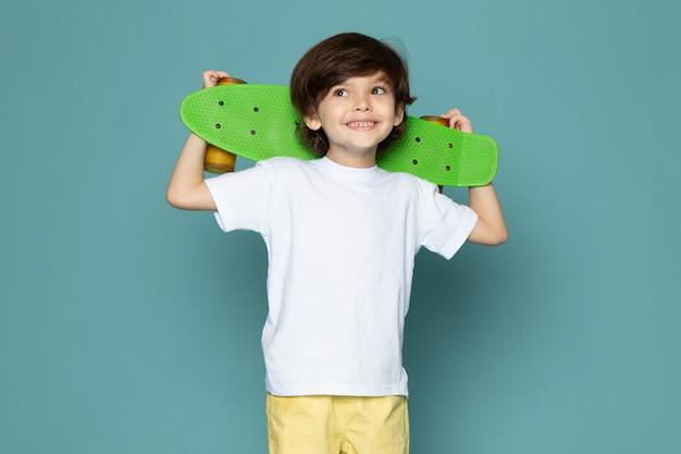 Ein niedlicher junge der vorderansicht im weißen t-shirt und in den gelben jeans, die grünes skateboard auf dem blauen raum halten