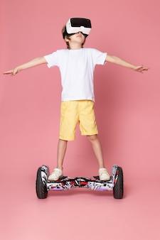 Ein niedlicher junge der vorderansicht im weißen t-shirt und in den orangefarbenen shorts, die segway auf dem rosa raum reiten