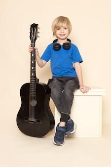 Ein niedlicher kleiner junge der vorderansicht, der im blauen t-shirt mit schwarzen kopfhörern mit schwarzer gitarre lächelt