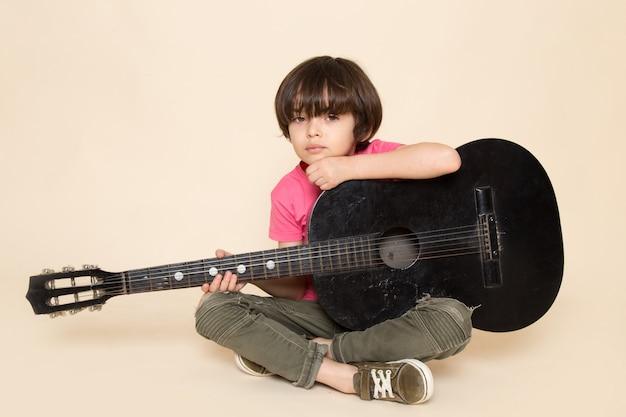 Ein niedlicher kleiner junge der vorderansicht, der in rosa t-shirt khaki jeans niedergedrückt wird, die schwarze gitarre spielen