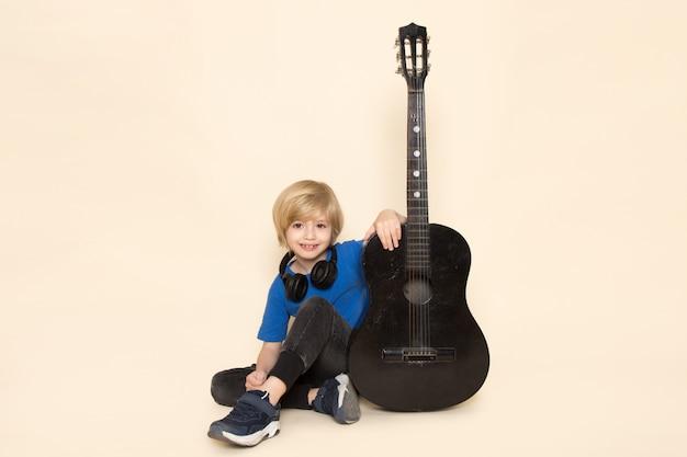 Ein niedlicher kleiner junge der vorderansicht im blauen t-shirt mit schwarzen kopfhörern, die schwarze gitarre halten