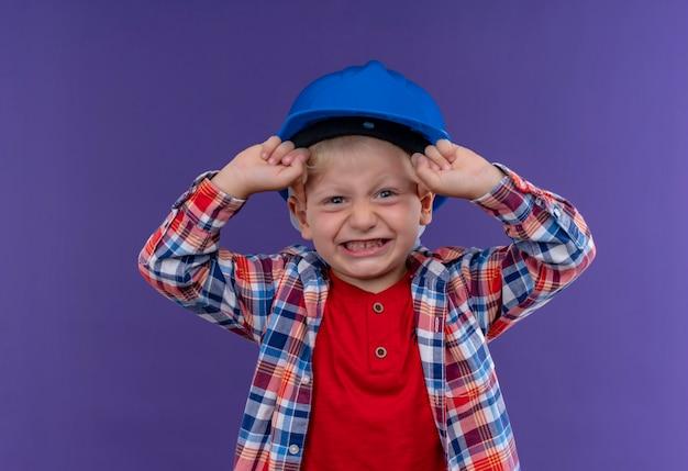Ein niedlicher kleiner junge mit blondem haar, der kariertes hemd im blauen helm trägt, der geballte fäuste erhebt, die auf eine lila wand schauen