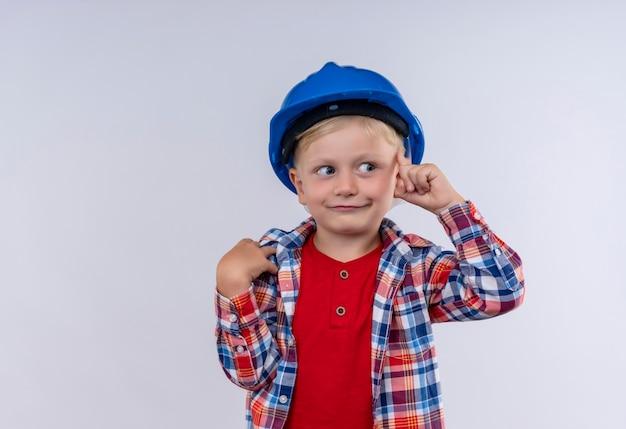 Ein niedlicher kleiner junge mit blondem haar, der kariertes hemd im blauen helm trägt, der mit zeigefinger auf einer weißen wand auf seinen kopf zeigt